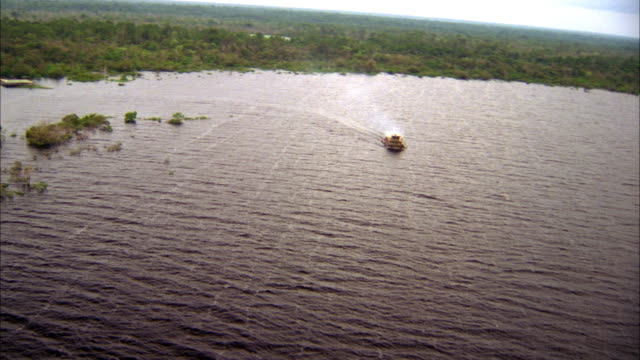 vidéos et rushes de aerial of brown boat on large body of water, possibly ocean. see small buildings from village on shore. - south america