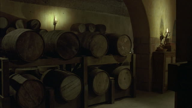 medium angle of dim lit wine cellar, basement. see brown oak wine barrels stacked against wall. see torches in background. - wine cask stock videos and b-roll footage
