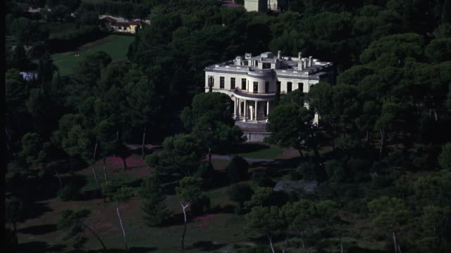 aerial of large two story white house with columns amidst forest. could be museum, historical site, mansion or villa. upper class. - cote d'azur stock videos & royalty-free footage
