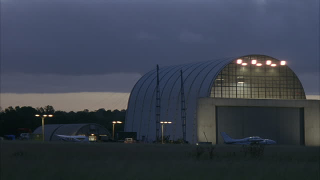 wide angle of hangar in small airport. small airplane in front of hangar. field in foreground. dark gray cloud. - small stock videos and b-roll footage