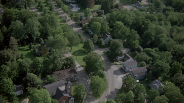 vidéos et rushes de aerial of suburbs with scattered houses and trees. follow main road through small town. pan left to continue following road. cars drive along with church on one side. - banlieue pavillonnaire