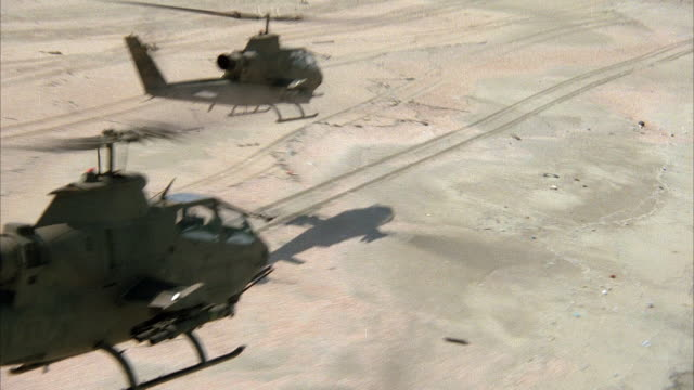 medium angle moving pov of two cobra military helicopters flying low above sand to right. middle east. attack helicopters. - kampfhubschrauber stock-videos und b-roll-filmmaterial