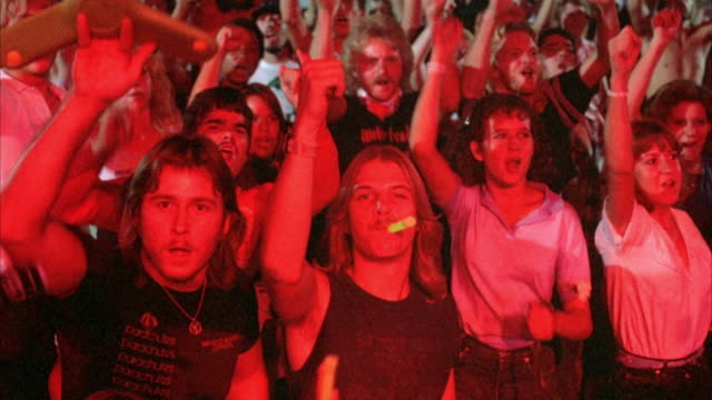 MEDIUM ANGLE OF CHEERING CROWD AT ROCK CONCERT. SEE FANS CLAPPING, CHEERING, AND DANCING TO MUSIC. BLURS A LITTLE AT BEGINNING OF SHOT.