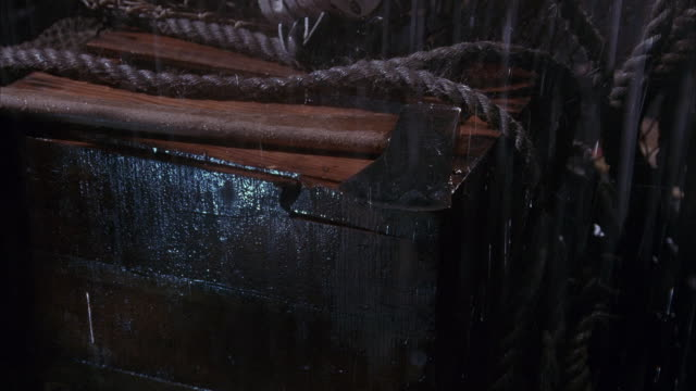 stockvideo's en b-roll-footage met medium angle of wooden box with thick rope and axe on it. see man in raincoat picks up axe. block and tackle visible. could be pier, warehouse, ship's deck or boat. - bijl