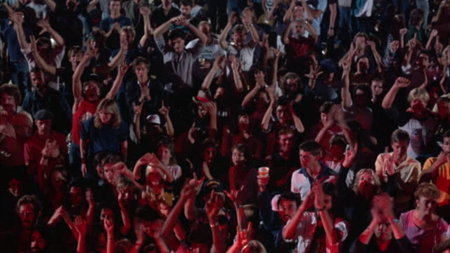 MEDIUM ANGLE SHOT OF CROWD AT ROCK CONCERT. SHOT PANS L TO R OF CROWD CHEERING, WAVING ARMS, DANCING. 1980'S STYLE HAIR AND DRESS. RED LIGHT REFLECTING OFF OF CROWD FROM STAGE LIGHTS.