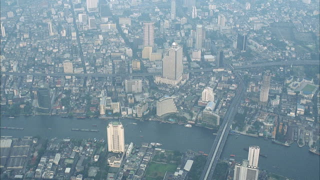 aerial of dense city. see tall multi story buildings mixed with small buildings. see thick haze. move down and see river with boats and tall buildings lining river. - bangkok stock-videos und b-roll-filmmaterial