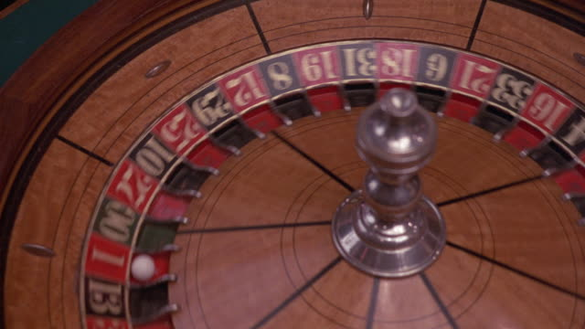 close angle of spinning roulette wheel, probably in casino. ball bounces around, then lands in one red as wheel comes to stop. insert. - casino roulette stock videos & royalty-free footage