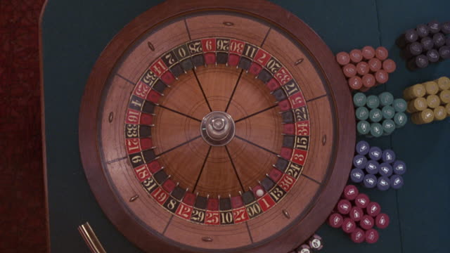 close angle of roulette wheel, probably in casino, with chips at right. ball in one red. croupier reaches and spins wheel, wheel slows and stops with ball in thirty five black. neg cut. - roulette stock videos & royalty-free footage