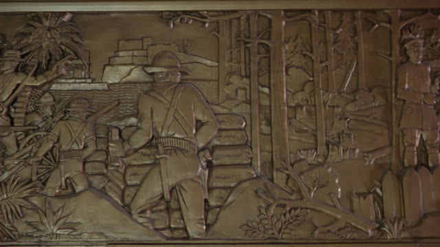 pan left to right of louisiana history and life a frieze at the louisiana state capitol building in baton rouge.  the sculpture depicts theodore roosevelt in the spanish american war - kapitol von louisiana stock-videos und b-roll-filmmaterial