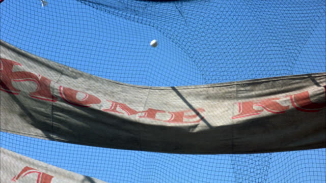 close angle up angle shot of  banners hanging up in front of baseball net to catch practice balls. banners are waving in the wind and read home run, triple, and double. baseballs shown hitting each of the banners. could be in a batting cage. - gabbia di battuta video stock e b–roll