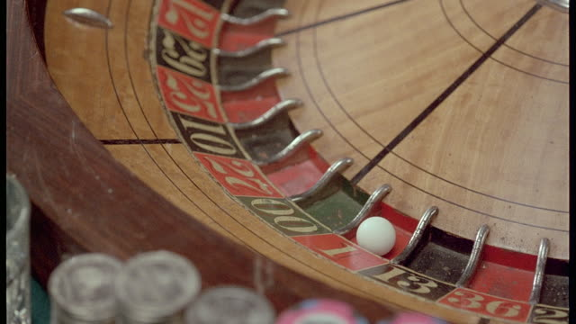 close angle of roulette wheel, probably in casino, with ball in one red. croupier reaches in and takes out ball, has another ball in his hand, possibly weighted. insert. - casino roulette stock videos & royalty-free footage