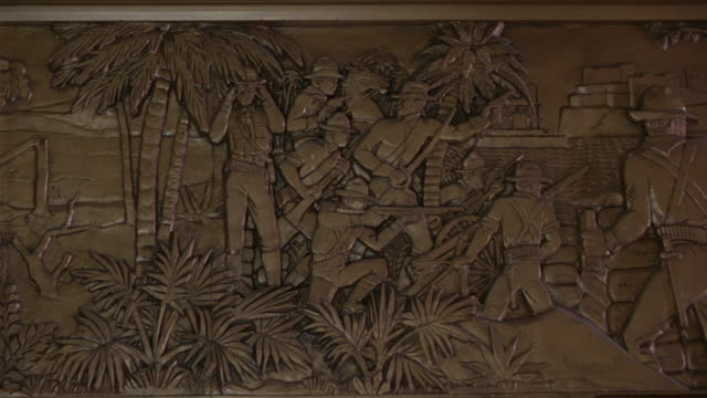 pan left to right of louisiana history and life a frieze at the louisiana state capitol building in bating rouge.  the sculpture depicts theodore roosevelt in the spanish american war - kapitol von louisiana stock-videos und b-roll-filmmaterial