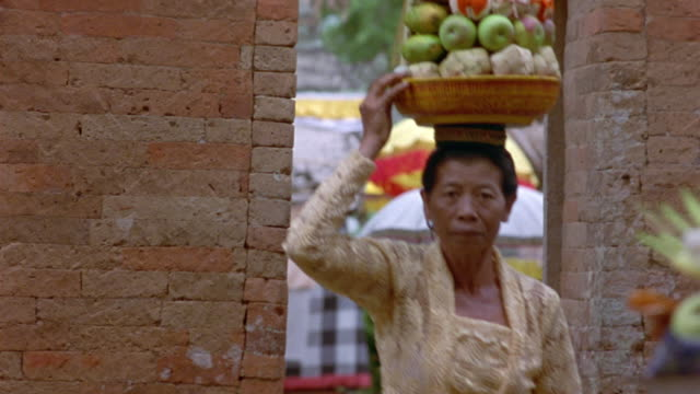 vídeos de stock, filmes e b-roll de medium angle of two older women walking through open doorway of brick wall, carrying baskets of fruit on their heads. multi-colored umbrellas can be seen through doorway in background. - tijolo material de construção