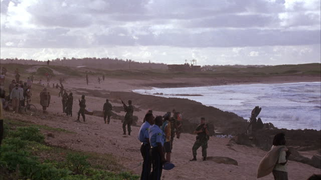 MEDIUM ANGLE OF SOLDIERS, GUARDS AND CIVILIAN PEOPLE ON BEACH. PEOPLE LOOK TOWARDS WATER.  SEE GUARDS BLOCKING PEOPLE FROM WATER. HELICOPTER PASSES OVER BEACH TOWARDS POV SEVERAL TIMES.