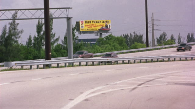medium angle driving pov on highway or freeway. shot pans right to left to billboard in background that says billie swamp safari. see passing vehicles on other side of highway. - florida usa stock videos and b-roll footage