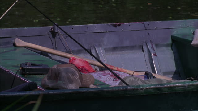 medium angle of fishermen covered in blood in rowboat in swamp. dead bodies and gore. - bloody gore stock videos & royalty-free footage