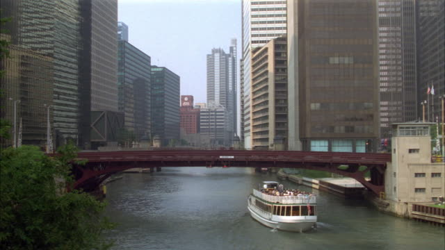 high angle down of chicago skyline and chicago river with crossing bridge. see boat passing underneath bridge. - chicago stock videos & royalty-free footage
