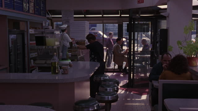 medium angle of cafe or restaurant. customers throughout restaurant. traffic moves along city street outside. restaurant counter on left. black stools around counter. booths on right. - anno 1999 video stock e b–roll