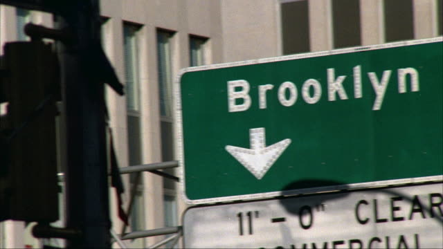close angle pan left to right of building in urban area, buss passes to right. pans right to street sign reading brooklyn br. insert. - road sign stock videos & royalty-free footage