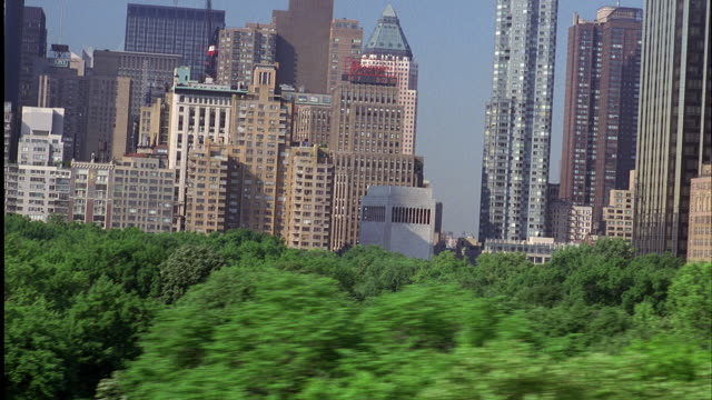 PAN RIGHT TO LEFT. HIGH RISE BUILDINGS IN MIDTOWN MANHATTAN. CENTRAL PARK TREETOPS IN FOREGROUND. PANS LEFT CAMERA LOWERS DOWN THROUGH TREES.