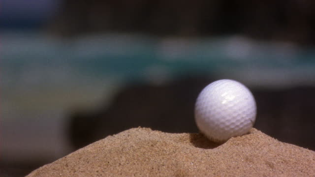 close angle of titleist golf ball landing in sand. could be bunker or sand trap on golf course. out of focus waves from ocean in bg. - golf ball stock videos and b-roll footage