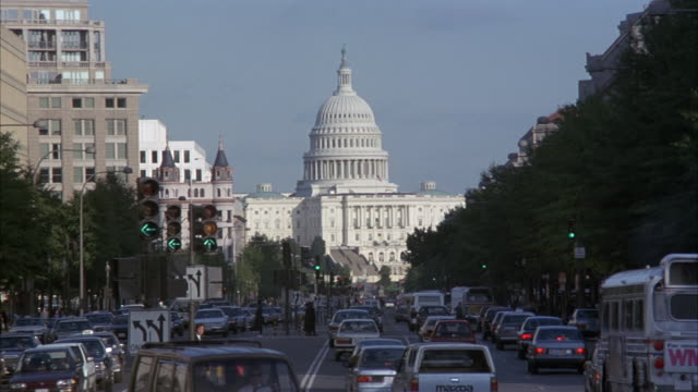 medium angle of us capitol building with city street in lower foreground leading up to building. see traffic in street. - washington dc stock videos & royalty-free footage