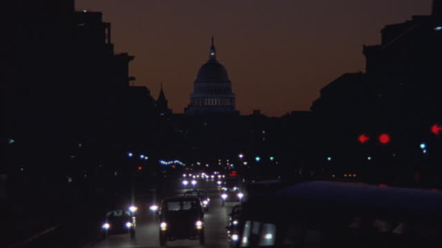 WIDE ANGLE OF ONE-WAY CITY STREET OR BOULEVARD FULL OF TRAFFIC, CARS AND BUSES. CAPITOL BUILDING ILLUMINATED IN BACKGROUND. ORANGE SKY. NEG CUT.