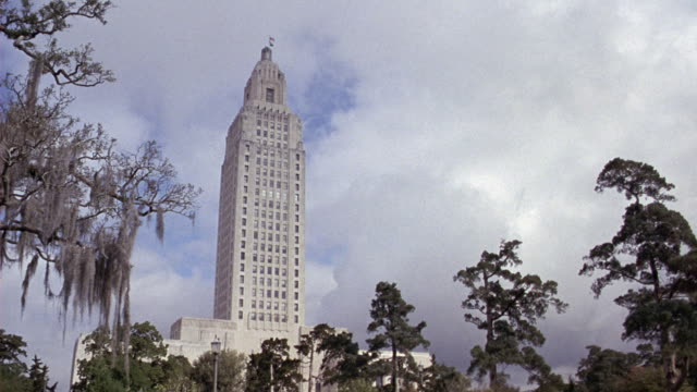 wide angle of the louisiana state capitol building in baton rouge.  the art deco skyscraper peeks above of the trees and spanish moss.  the cloudy sky above moves slowly. government buildings. filmed 12fps. - baton rouge stock-videos und b-roll-filmmaterial