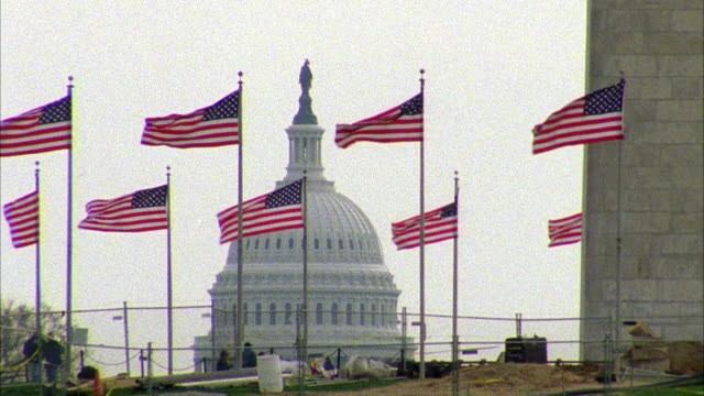 WIDE ANGLE ON THE DOME OF THE CAPITOL BUILDING OR GOVERNMENT OFFICE BUILDING BEHIND A SERIES OF AMERICAN FLAGS IN FG. CONSTRUCTION SITE. WEST POTOMAC PARK.