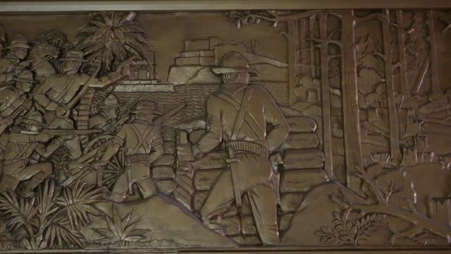 pan left to right of louisiana history and life a frieze at the louisiana state capitol building in bating rouge.  the sculpture depicts theodore roosevelt in the spanish american war, - kapitol von louisiana stock-videos und b-roll-filmmaterial