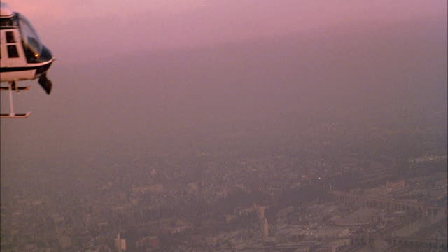 vidéos et rushes de pan up of smog covering city to police helicopter, then up to blue sky. - smog