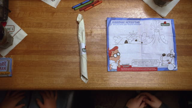 high angle down of table at applebee's restaurant. waiter or waitress places food on table, chicken tenders and cheeseburger with french fries. children sit at booth. crayons, glasses, coloring placemat - 1989 stock videos and b-roll footage