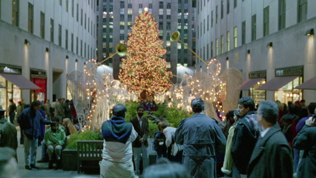 medium angle of crowd in rockefeller center. see giant christmas tree in center background. tourists flash cameras, shops on sides. - rockefeller center christmas tree stock videos & royalty-free footage