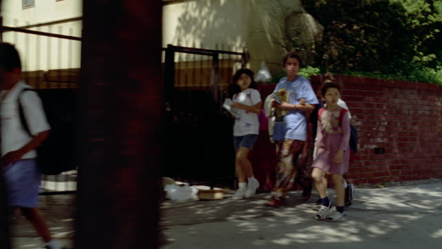 MEDIUM ANGLE MOVING POV OF CHILDREN OR STUDENTS WALKING HOME FROM SCHOOL ALONG SIDEWALK. SEE BRICK WALL IN BACKGROUND. PROBABLY LOWER CLASS AREA.