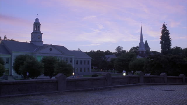 wide angle of cobblestone bridge, church and town hall. see steeple of church sticking out from among trees. - steeple stock videos & royalty-free footage