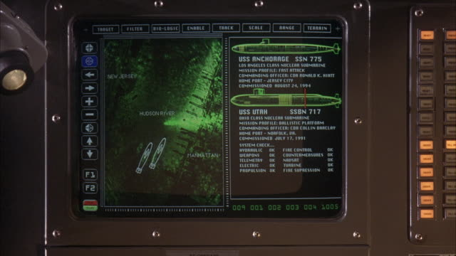 MEDIUM ANGLE OF COMPUTER MONITOR WITH GREEN GRAPHIC OF SATELLITE PICTURE OF HUDSON RIVER ON LEFT OF SCREEN. ON RIGHT OF SCREEN THREE IMAGES OF SUBMARINES APPEAR WITH NAMES USS ANCHORAGE AND USS UTAH AND USS ARIZONA. SILVER BORDER TO COMPUTER SCREEN.
