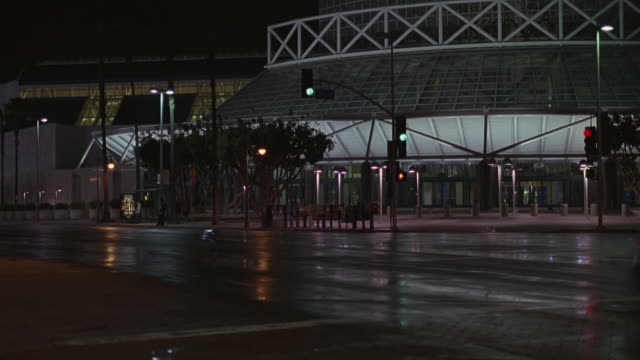 stockvideo's en b-roll-footage met pan left to right as an suv car drives past the staples center basketball arena or stadium in downtown los angeles. also used as a concert hall or venue. the car also passes the convention center. - los angeles convention center