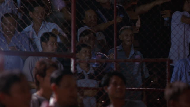 MEDIUM ANGLE OF CROWD CHEERING THROUGH A CHAIN LINK FENCE AT AN ARENA IN THAILAND OR ASIA. COULD BE CHEERING FOR FIGHT OR BOXING MATCH. SEE YOUNG AND OLD MEN CHEERING AND THROWING HANDS IN AIR.