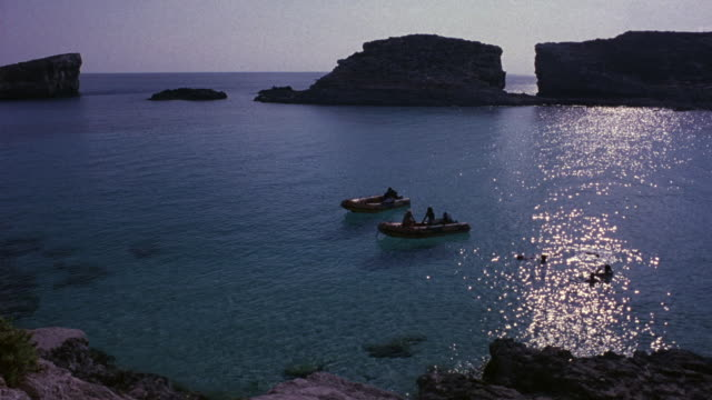 medium angle of mediterranean sea cove. see two dinghies with passengers inside. see people swimming in ocean water next to boat. water is very blue and clear. see large brown boulders of isolated cove or island in foreground and background. - sardinien stock-videos und b-roll-filmmaterial