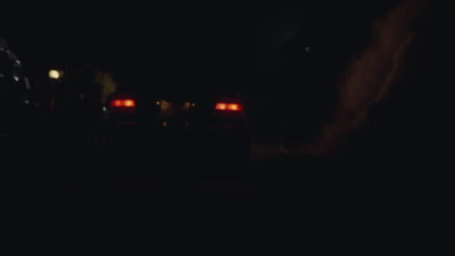 WIDE ANGLE OF TAIL LIGHTS OF BMW ON COUNTRY ROAD. LICENSE PLATE VISIBLE. CAR PEELS OUT AND SPINS AROUND IN OPPOSITE DIRECTION WITH HEADLIGHTS ON.