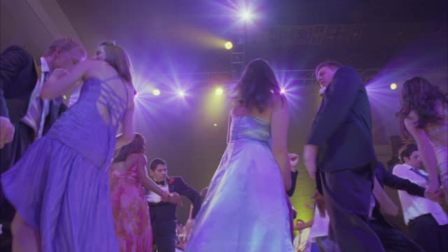up angle of teenagers in evening gowns and tuxedos dancing at prom celebration and party. confetti falling from ceiling. - 高校卒業ダンスパーティ点の映像素材/bロール