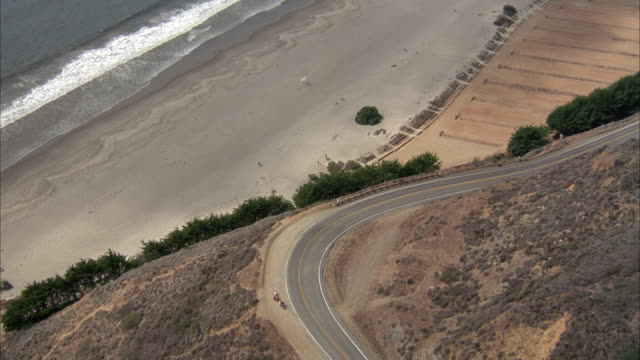 aerial of coastal road next to beach and ocean, red convertible drives in from left and frame zooms in slightly on car. - convertible stock videos & royalty-free footage