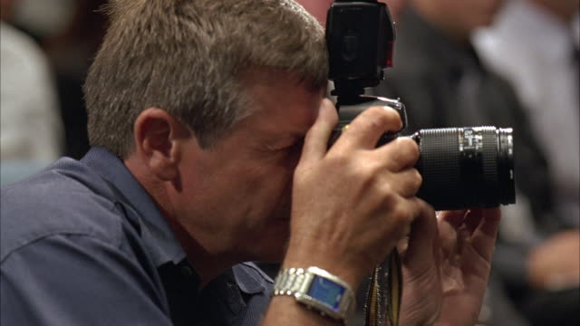close angle of man using still camera. photographer could be press. camera has external flash attached. pan left to women reporter also in the conference room or press room - photographer stock videos & royalty-free footage