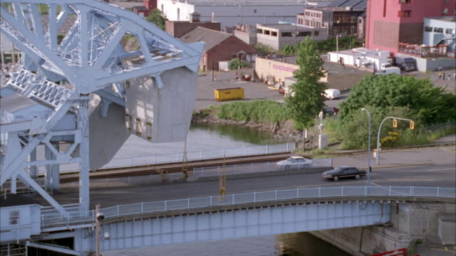 tracking shot of a dark blue crown victoria as it passes over drawbridge. see boats docked in water below. see port and dock warehouses in background. - drawbridge stock videos and b-roll footage