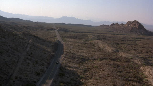 vídeos de stock, filmes e b-roll de aerial of dark car or truck driving on desert road. mountains in background. could be blue, green, or black. - sudoeste dos estados unidos