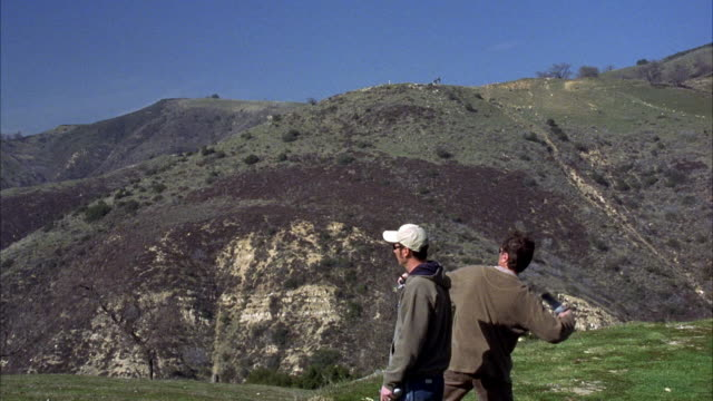 hand held. set in elysian park. pov from top of hill. see trainer holding pigeon, throws into air. shot tracks pigeon as it flies into air. zooms in on pigeon at end. - mit handkamera stock-videos und b-roll-filmmaterial