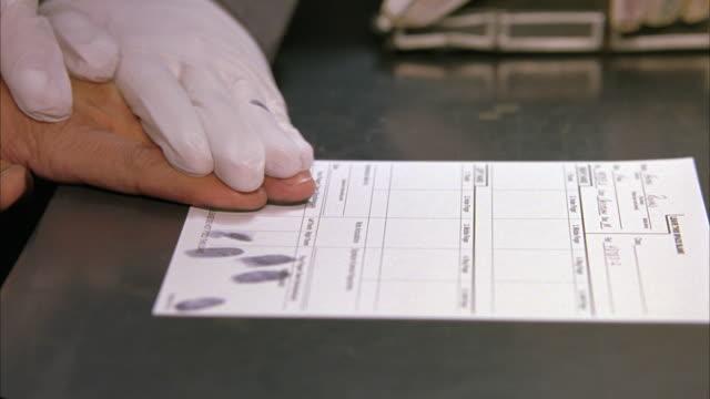 close angle of criminal fingerprinting in ink. fingerprints on paper in police station. - fingerprint stock videos & royalty-free footage