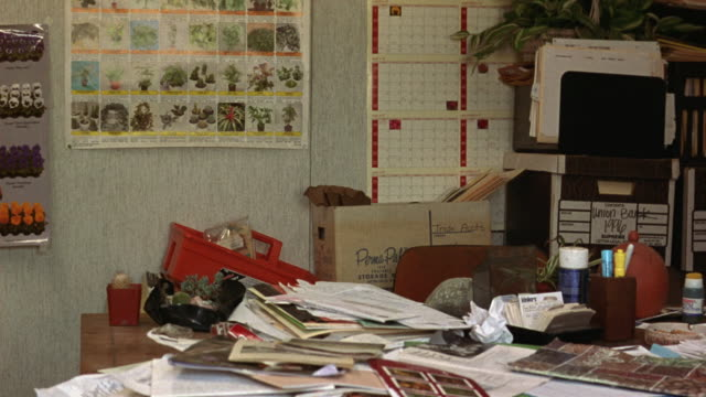 medium angle office area. see cluttered desk against wall with piles of papers, envelopes, boxes and files. see two posters with various flower types and a calendar posted on wall. - desk stock videos & royalty-free footage