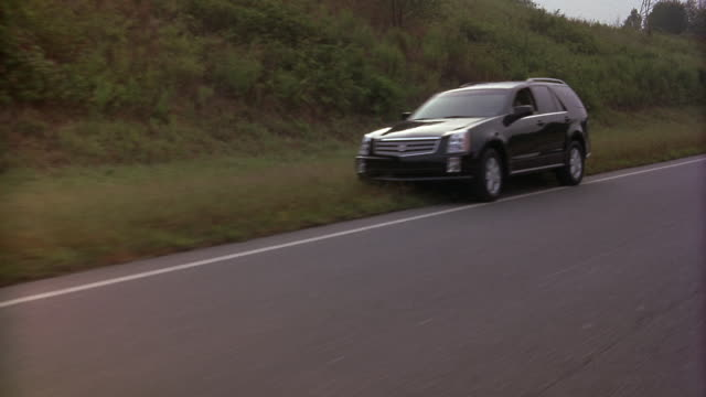 wide angle driving pov passing a black cadillac srx suv with a flat tire on the wide of the road. man is outside, appearing to fix the flat. suv is on the shoulder with hazard lights flashing. - vehicle breakdown stock videos and b-roll footage