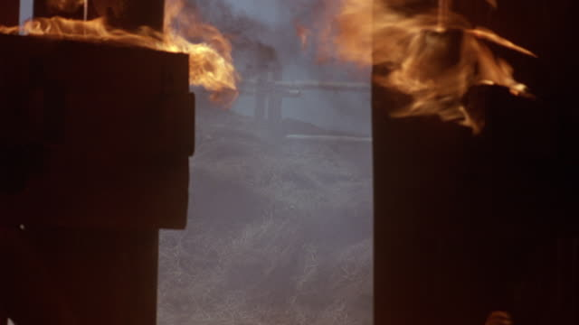 MEDIUM ANGLE OF CABIN ON FIRE. SEE CABIN DOORS IN FOREGROUND. CAMERA IS TILTED TO LEFT. SEE BURNING CABIN DOORS, FLAMES. SEE BROWN HORSE, COULD BE FOAL, RUNNING BACK AND FORTH OUTSIDE OF CABIN.